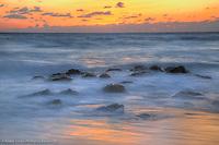 Sunrise and Atlantic Ocean flowing over rocks, near Palm Beach, Florida