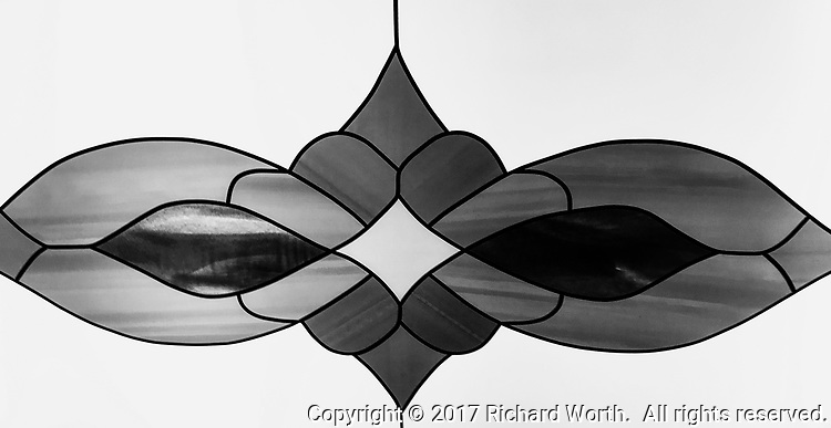 The lightpanels on an elevator ceiling provide lines and shapes, shades and tone, like a stained glass creation rendered in plastic.  Imaage converted to black and white.