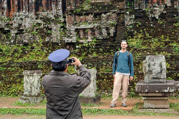 Asia, Vietnam, My Son near Hoi An. Tourist being photographed by a helpful guard within the temple ruins of group B. Designated a Unesco World Heritage Site, the temple complex of My Son is located in a dense, vegetaded valley beneath Hon Quap or Cat's Tooth Mountain. Having been a religious center from the 4th to the 13th century, today traces of ca. 70 temples may be found, though only about 20 are in good condition. The monuments are divided into 10 groups.