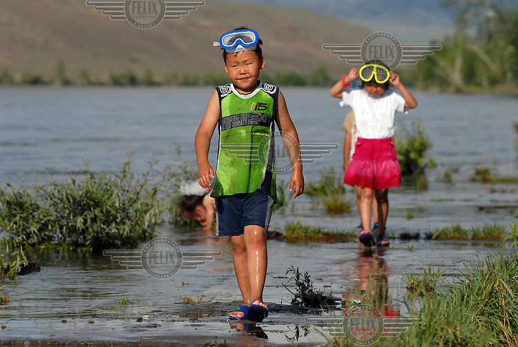 Children walk along the banks of the Yenisei River in Kyzyl..