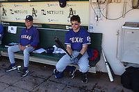 OAKLAND, CA - SEPTEMBER 22:  Coach Jackie Moore #4 and Ian Kinsler #5 of the Texas Rangers get ready in the dugout before the game against the Texas Rangers at O.co Coliseum on September 22, 2011 in Oakland, California. Photo by Brad Mangin