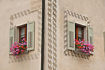 Windows with green shudders and pink flowers in the small town of Viscoprano, a Swiss town in the Bregaglia Valley which dates back to 1096. The decorations on the house are patterns scratched out of the still wet wall, decorative artwork called sgraffiti, traditionally done in two colors and originating in Italy, brought to the Engadin region of Switzerland in the 16th century and is still used today