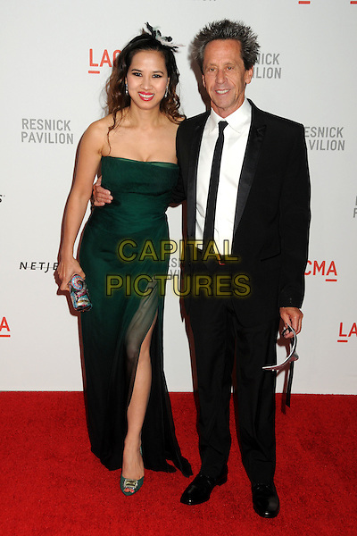 "BRIAN GRAZER & GUEST .LACMA's ""The Unmasking"" of the Lynda & Stewart Resnick Exhibition Pavilion Opening Gala held at the Los Angeles County Museum of Art, - Los Angeles, California, USA, 25th September 2010..full length strapless green dress long maxi suit black tie slit split .CAP/ADM/BP.©Byron Purvis/AdMedia/Capital Pictures."