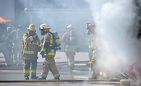 NWA Democrat-Gazette/ANDY SHUPE<br /> Mauro Campos (left), battalion chief for the Fayetteville Fire Department, speaks with participants Wednesday, March 7, 2018, as a training fire burns during a workshop for fire department leadership to meet current National Fire Protection Association standards at the Fayetteville Fire Department training facility in south Fayetteville. Thirty students and instructors from agencies in seven states attended the training meant to train department training officers at current standards.