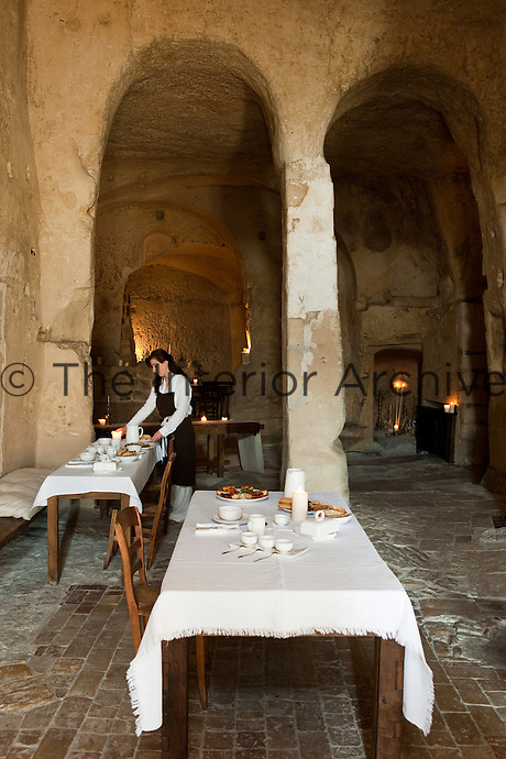 The dining room, here being prepared for breakfast by a waiteress, is housed in a former church at the unique Albergo Diffuso Le Grotte della Civita in Southern Italy