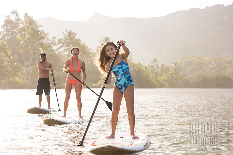 A family has fun during their standup paddling lesson on Wailua River, Kaua'i.