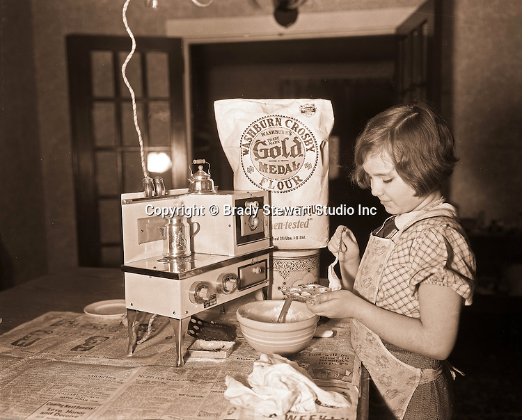 Wilkinsburg PA:  Young girl baking cookies with a new electric oven and Gold Metal flour - 1919