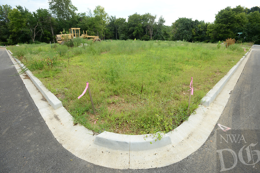 NWA Democrat-Gazette/ANDY SHUPE<br /> A grader stands Tuesday, Aug. 13, 2019, in an empty lot at the Homes at Willow Bend project, a development by Partners for Better Housing.The project involves building about 80 homes for families of mixed incomes with affordable financing available. It broke ground in 2017.
