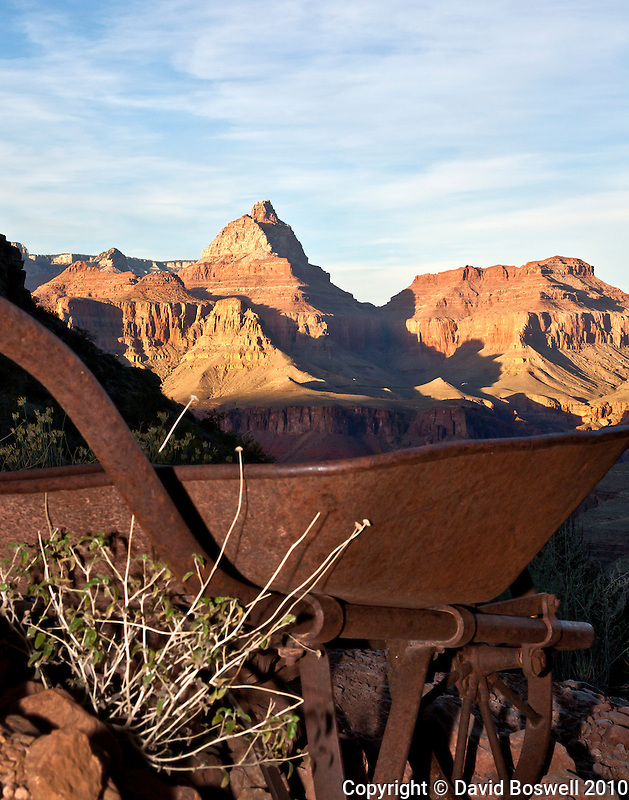 A rusted wheelbarrow, a remnant from the Last Chance Mine, marks the spur trail to Page Spring, a major water source for backpackers on Horseshoe Mesa in the Grand Canyon.  Vishnu Temple stand lit in the setting sun in the background.