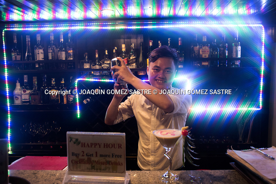 A waiter prepares a cocktail in one of the hundreds of tourist cruises that cross the bay of Ha Long (vietnam)<br /> HALONG-VIETNAM