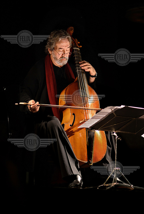 A portrait of conductor and composer Jordi Savall i Bernadet playing a cello at Pedralbes Monastery in Barcelona.