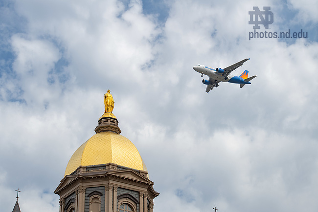 April 12, 2018; An airliner flies over the Golden Dome on its way to land at South Bend International airport. (Photo by Matt Cashore/University of Notre Dame)