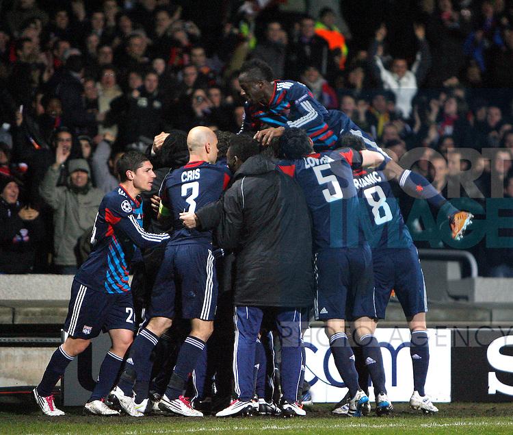 Lyon players mob Bafetibis Gomis after scoring his equalising goal