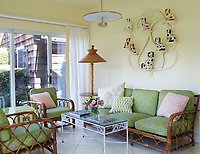 In the garden room, cane seating with green cushions is arranged around a metal coffee table. A collection of Staffordshire pottery is displayed on a wall shelf unit.