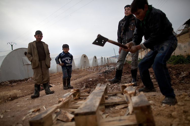 Boys take turns chopping a wooden pallet to use for firewood at Azaz Camp, just in side the Syrian border with Turkey, Feb. 22, 2013. According to administrators, this camp holds roughly 9,000 to 10,000 internally displaced persons (IDP's). Some food is provided by a Turkish humanitarian organization, and Qatar Red Crescent provided tents. There is very little electricity, and no running water. The UN Refugee Agency has reported a sharp increase in refugees fleeing Syria for neighboring countries in the first months of 2013.