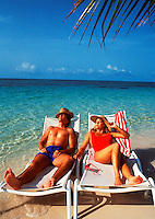 Totally relaxed couple on the beach in lounge chairs