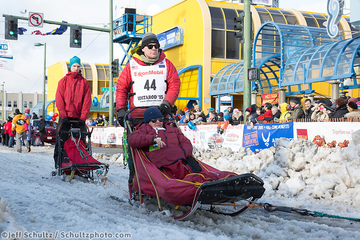 Gerald Sousa and team leave the ceremonial start line with an Iditarider at 4th Avenue and D street in downtown Anchorage, Alaska during the 2015 Iditarod race. Photo by Jim Kohl/IditarodPhotos.com