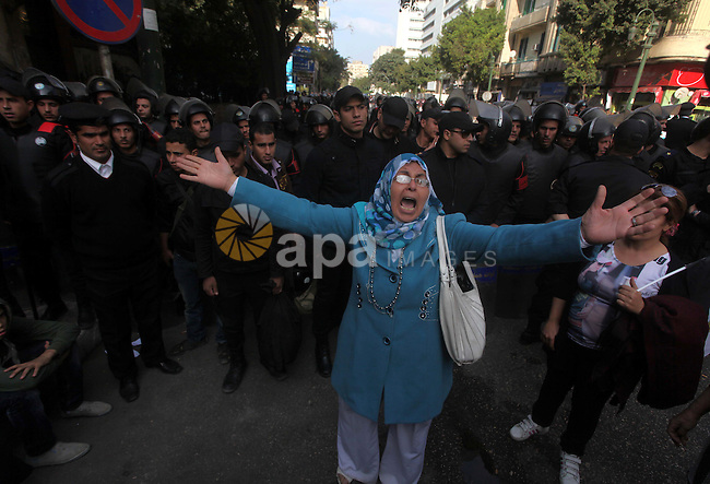 Egyptians women protest against the  police officers near the Shura Council, the upper house of parliament where the Constituent Assembly drafted the country's new constitution, as protesters against Egypt's President Mohamed Morsi chant slogans in front of them, while Morsi gives a speech before a newly empowered senate in Cairo on December 29, 2012. Morsi said in the address, a disputed new constitution guaranteed equality for all Egyptians, and downplayed the country's economic woes. Photo by Ashraf Amra