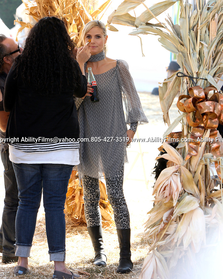 ..October 11th 2011..Heidi Klum posing with pumpkins at Mr.Bones pumpkin patch in Los Angeles. Laughing stabbing the pumpkin with a knife while she carved it. Heidi was goofing around  wearing the top piece of the pumpkin on her head. Hiedi wore long black leather boots tight spandex cheetah leopard print pants see through scarf shirt getting makeup put on while drinking a coca cola & holding a skull ...AbilityFilms@yahoo.com.805-427-3519.www.AbilityFilms.com