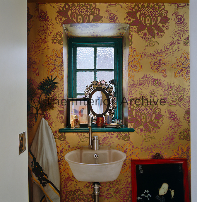 Looking through the doorway into the small bathroom which is with decorated with gold floral wallpaper
