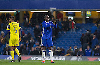 Kurt Zouma of Chelsea applauds the supporters after completing his first full 90 minutes after injury layoff a disappointed Curtis Nelson of Oxford United walks away after Chelsea's 13-12 penalty shootout win as a record 34 spot-kicks are taken during the The Checkatrade Trophy match between Chelsea U23 and Oxford United at Stamford Bridge, London, England on 8 November 2016. Photo by Andy Rowland.