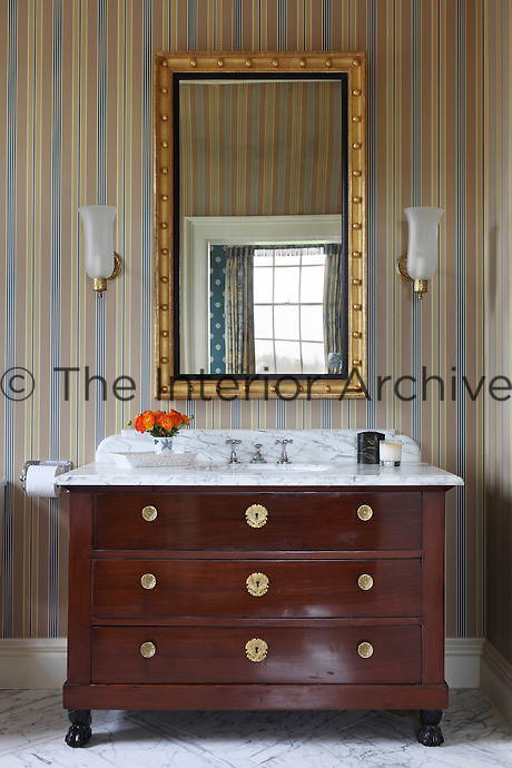 A Georgian striped bathroom with an antique marble-topped washstand/chest of drawers