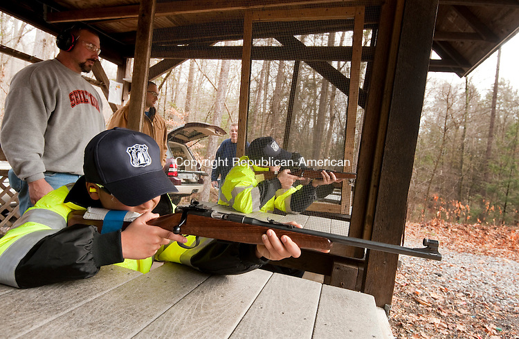 NAUGATUCK, CT--- -112215JS06--Gun range member and instructor Dave Kudej of Shelton, left, looks on as members of the Waterbury Police Explorers, including Alex Rodriguez, front, train their weapons down range while shooting during a visit to the High Rock Shooting Range in Naugatuck on Sunday. The visit was to teach the explorers gun safety and then a target shooting session.<br /> Jim Shannon Republican-American