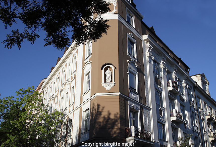 Corner Building in old Architecture, showing a white Sculpture. Backdrop blue summer sky.