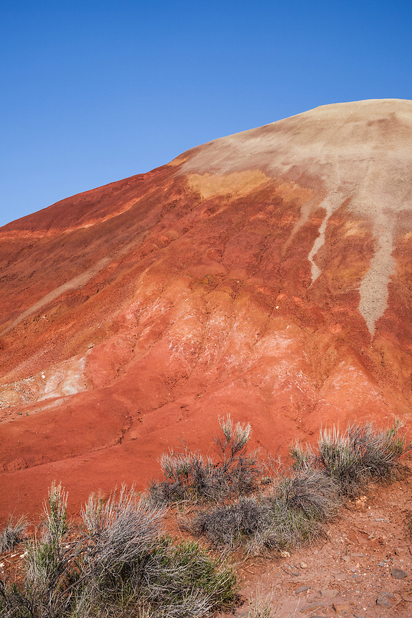 A reddish, rust-colored hill is seen in the afternoon light at the Painted Hills section of the John Day Fossil Beds in Wheeler County, Oregon.
