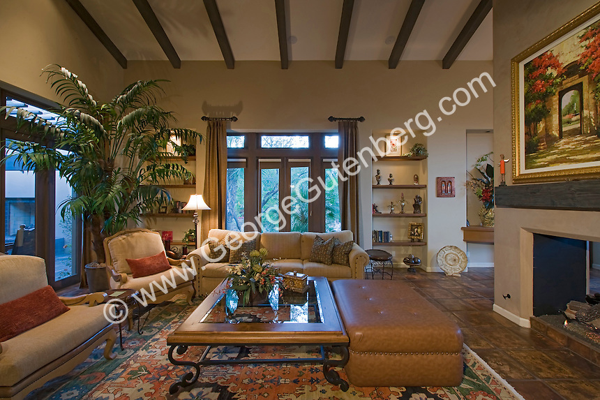 Mediterranean style family room featuring wood beamed cielings, elegant furnishings, and warm colors.