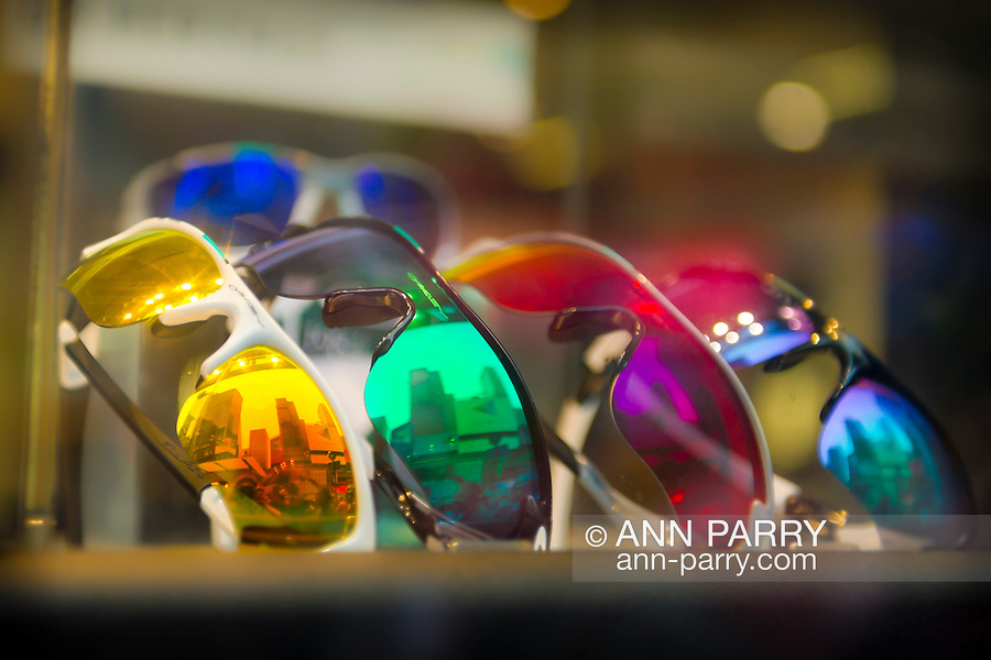 Manhattan, New York, U.S. - May 21, 2014 - In the Oakley sunglasses store window display, 5 colorful sunglasses reflect the 7th Avenue buildings of midtown Manhattan, during a pleasant Spring day, though skies were gray.
