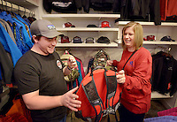 STAFF PHOTO BEN GOFF  @NWABenGoff -- 12/26/14 Jake Coe, store manager, helps Charity Dezurik of Gravette pick out a daypack while she shops with gift cards she received as presents in Grearhead Outfitters at Pinnacle Hills Promenade in Rogers on Friday Dec. 26, 2014.