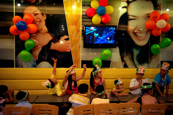 Children play during a party inside a newly opened KFC fast food restaurant in Buon Ma Thot, VIetnam on 2 March 2010.