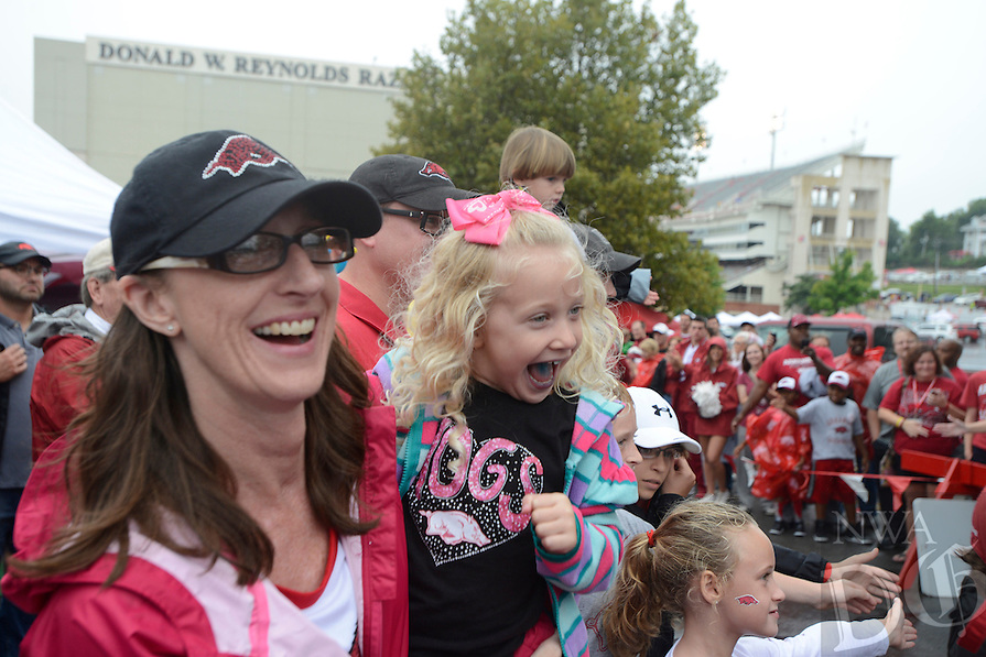 STAFF PHOTO ANTHONY REYES &bull; @NWATONYR<br /> Julie Casey, and her daughter Hensley Casey, 3, both of Bentonville, cheer Saturday, Sept. 6, 2014 as the University of Arkansas football team passes by in lot 56 in Fayetteville. This is the first home game of the season and the Razorbacks hope to break a 10 game losing streak.