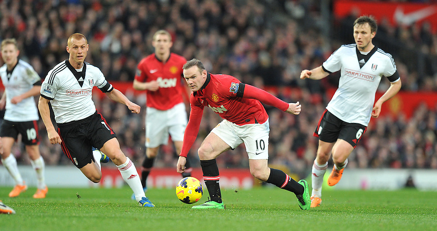 Manchester United's Wayne Rooney flanked by Fulham's Steve Sidwell (left) and William Kvist (right)<br /> <br /> Photo by Dave Howarth/CameraSport<br /> <br /> Football - Barclays Premiership - Manchester United v Fulham - Sunday 9th February 2014 - Old Trafford - Manchester<br /> <br /> &copy; CameraSport - 43 Linden Ave. Countesthorpe. Leicester. England. LE8 5PG - Tel: +44 (0) 116 277 4147 - admin@camerasport.com - www.camerasport.com