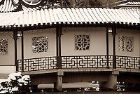 Covered bridge and walkway over pond, with snow-covered tile roof, ornate carved railings and window openings, in winter, Dr. Sun Yat Sen Classical Chinese Garden and Park, Chinatown, Vancouver, BC.
