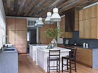 There are time-honoured materials in the kitchen, which is outfitted with soapstone countertops and backsplash, stainless steel appliances, and twin islands sheathed in statuary marble. The kitchen's cupboards are clad in a wormy chestnut that has been brushed with a faint white wash and embellished with handsome burnished-nickel pulls. The kitchen stools and pendant lights are from Ann-Morris Antiques, the range is by Wolf, and the ceiling is covered in reclaimed barn siding.