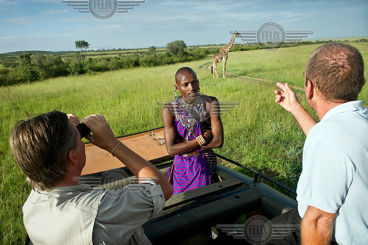 Jeff Natekinye ole Sadera (28). During the day he works as a tour guide, showing tourists all the wild animals which previous generations Masai used to hunt because they were a threat to their cattle. Jeff wears a traditional outfit with two tourists in a safari van, in the background is a giraffe. Masai communities are living on the edges of the National Park. Traditionally they move around with their cattle and goats and sheep. But urbanization, expanding agricultural sector on one hand and the National Park on the other, their space is diminishing. In dry seasons they are forced to graze their animals inside the National Park, despite the risk to be fined by the Rangers.