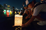 A boy sets a floating candle lantern on the river on August 6, 2015, in Hiroshima, Japan. The lanterns, thousands of which were launched on the 70th anniversary of the atomic bombing of the city, carried handmade messages and drawings, conveying each person's prayers for peace and comfort for the victims of the violence.