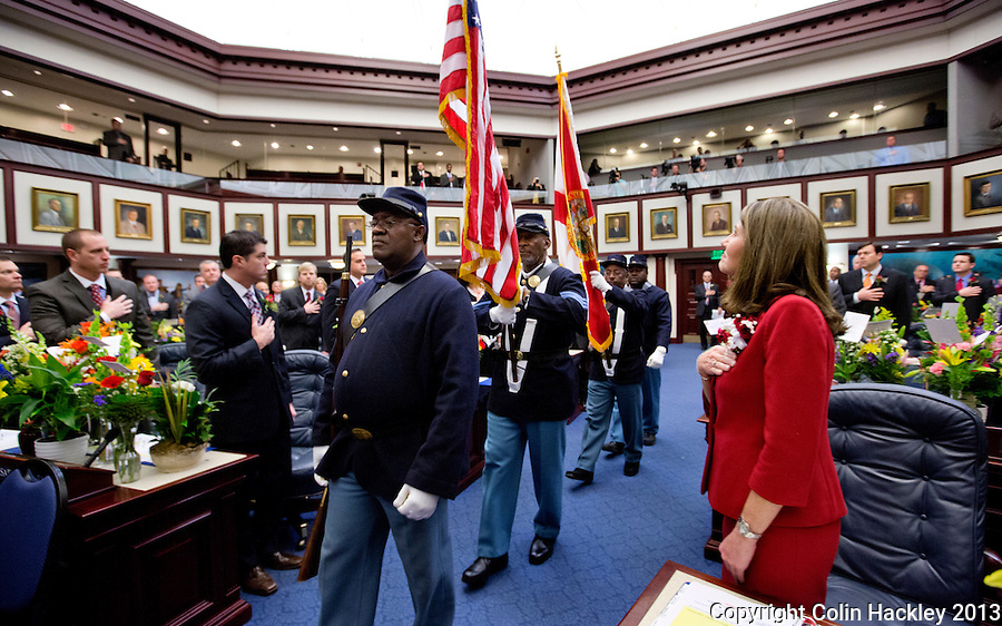 TALLAHASSEE, FLA. 3/5/13-OPENING030513CH-Rep. Marti Coley, R-Marianna, right, wathces as members of the U.S. Colored Troops 2nd Infantry reenactment group carry the colors into the House Chamber during the opening day of the 2013 legislative session Tuesday at the Capitol in Tallahassee, Fla. The group, made up of retired military pays tribute to the freed slaves who served in the Union Army and fought at the 1865 Battle of Natural Bridge south of Tallahassee..COLIN HACKLEY PHOTO
