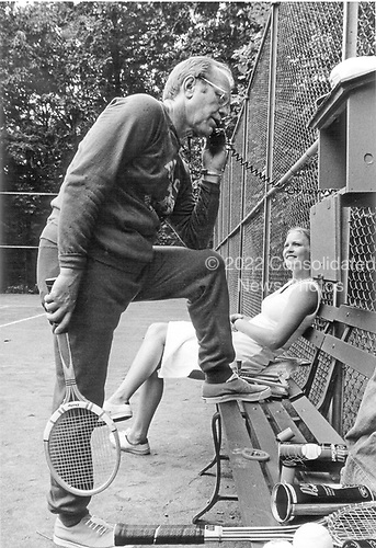 Even during a break on the tennis court at Camp David, United States President Gerald R. Ford keeps in touch with his work.  Behind him is his daughter, Susan, who also shares the President's love for sports.  On September 1, 1974, the first of their two visits in 1974 to the Presidential retreat near Thurmont, Maryland, the President and his daughter had a chance to play several sets of tennis together.  <br /> Mandatory Credit: David Hume Kennerly / White House via CNP