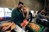 Feb. 20, 2019. San Diego, CA. USA| Volunteers Brett Lillie and Micayla Lillie unbox container damaged food products like crackers to turn into hog feed at the Feeding San Diego.  | Photos by Jamie Scott Lytle. Copyright.