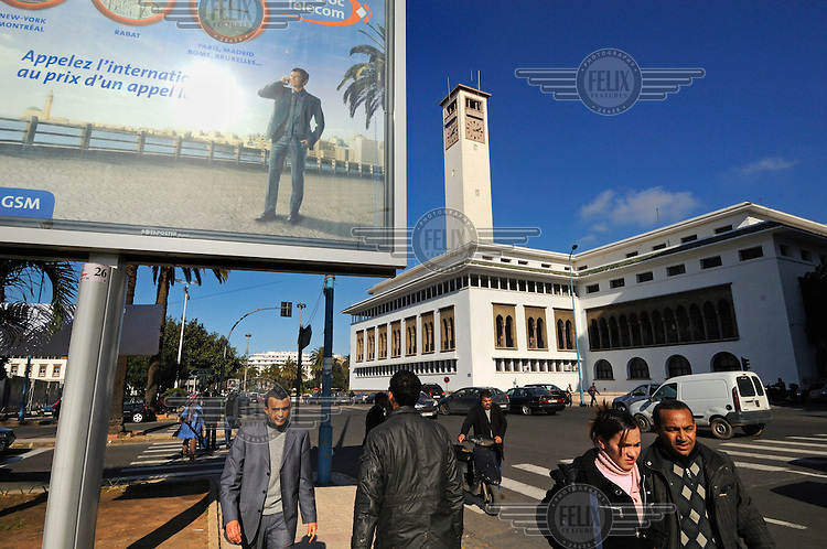 Pedestrians walk past a Maroc Telecom advertising billboard in the centre of Casablanca. To the right is the Prefecture Building (City Hall), an example of Mauresque architecture, a confluence of French and Moorish styles.