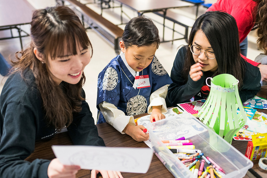 Volunteers from UW-Madison's Korean American Student Association (KASA) help a child with a craft project during a lunar new year event hosted by Families Through Korean Adoption (FTKA) in the gym and school cafeteria of St. Dennis Church in Madison, Wis., on Feb. 10, 2018. The event celebrated the passing of the lunar new year, and is one of several events for FTKA-member families and children to gather and enjoy cultural fun, food and play. (Photo by Jeff Miller - www.jeffmillerphotography.com)