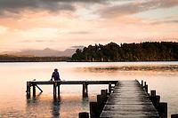 Lake Mahinapua near Hokitika at sunset with person on jetty, South Westland, West Coast, New Zealand