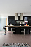 In the kitchen/living area a soft tufted rug contrasts with glossy black parapan cupboards and mellow grey stone floors