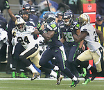 Seattle Seahawks running back Robert Turbin (22) runs for a 37-yard gain against the New Orleans Saints Corey White (24) and Rafael Bush (25) during  the 2nd round in a NFL Western Division playoff game at CenturyLink Field in Seattle, Washington on January 11, 2014.  Seahawks beat the Saints 22-15 to take home-field advantage in the NFL Championship Game. ©2014. Jim Bryant Photo. ALL RIGHTS RESERVED.