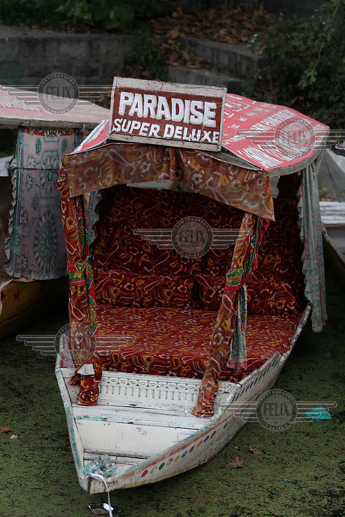 Shikara, a water taxi, parked at the waters edge. The boat is named Paradise Super Deluxe, contrasting the polluted waters and poor surroundings where it was moored.  Srinagar, Kashmir, India. © Fredrik Naumann/Felix Features
