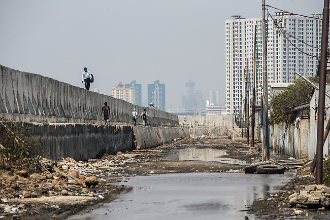 13 August 2019, Jakarta, Indonesia: Local residents walk on the protective seawall barrier keeping the ocean at bay at Muara Baru, North Jakarta. Built by Governor (now President) Joko Widodo it was constructed to prevent further encroachment by the ocean into the settlements in North Jakarta which is sinking at a rate faster than anywhere else in the world. Residents speak of the flooding  that would drive them to higher ground washing away all in its path. Residents now say the land is dry and usable but it is an ongoing crisis for Indonesia. Picture by Graham Crouch/The Telegraph