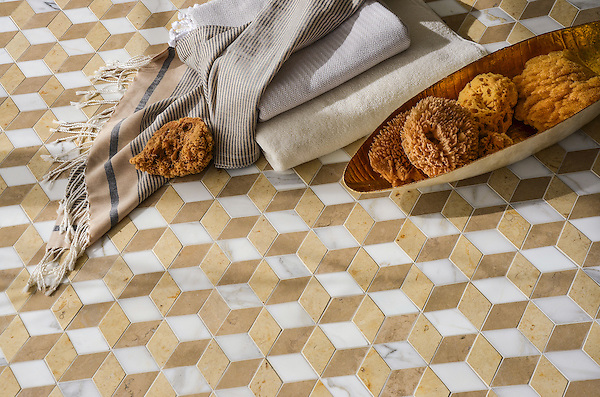 Euclid Grand, a hand-cut mosaic shown in polished Calacatta, honed Sylvia Gold  and honed Lagos Gold, is part of the Illusions® collection by New Ravenna.